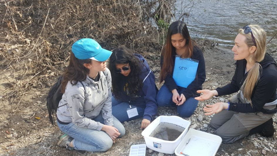 Students by the river informed by a professional on water quality testing.