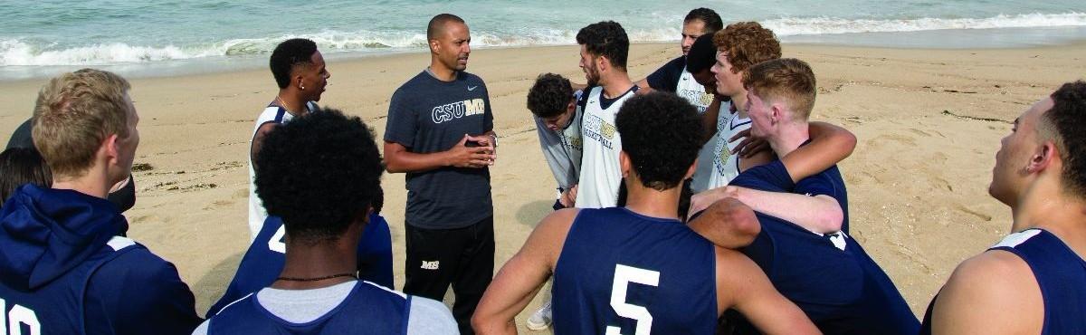 CSUMB men's basketball team huddles at the beach after a workout