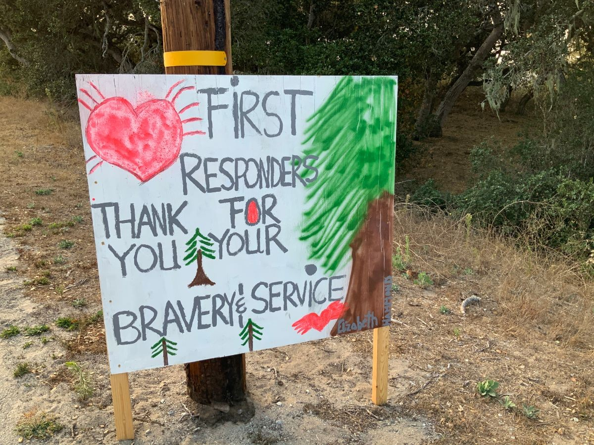 """A child's sign reads """"First responders, thank you for your bravery & service."""""""