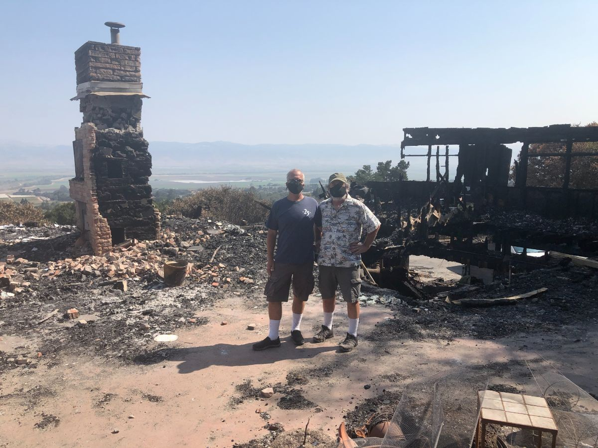 Chip Lenno and Kevin Cahill at the charred remains of their house.