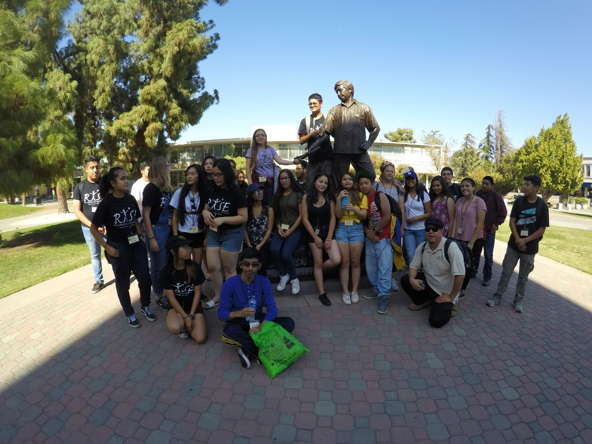 Students gather around the a statue at CSU Fresno.