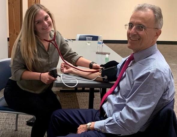 President Eduardo Ochoa receives blood pressure check from MSPA student