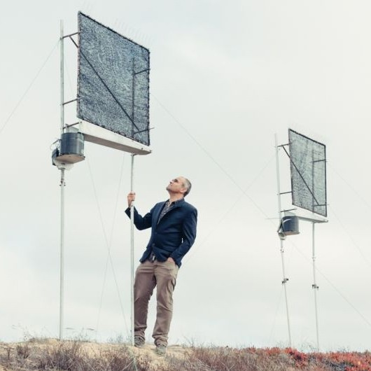 Dr. Daniel Fernandez standing next to his fog water catchers on CSUMB's campus