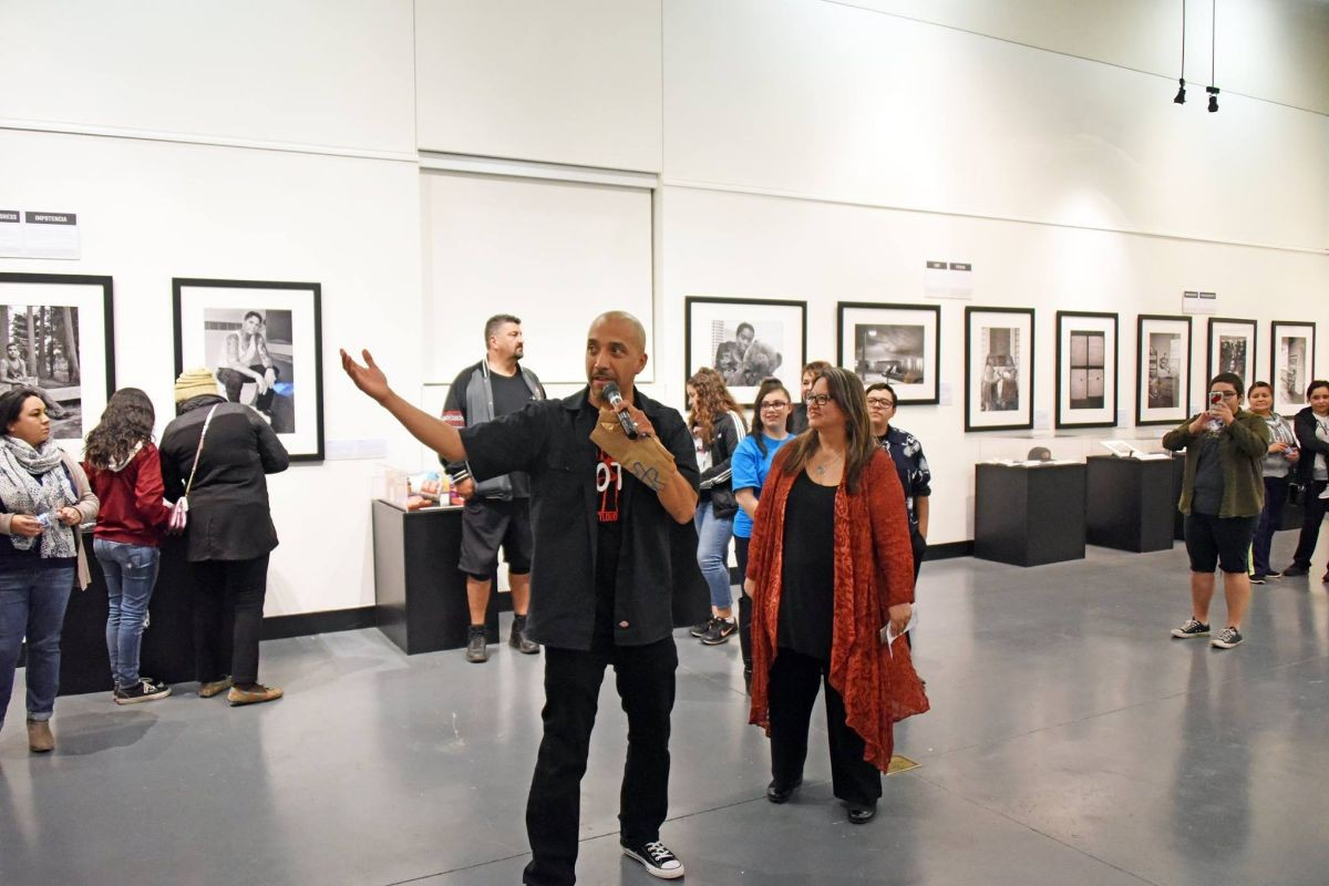 Everyone looking at the man making a speech in an art gallery.