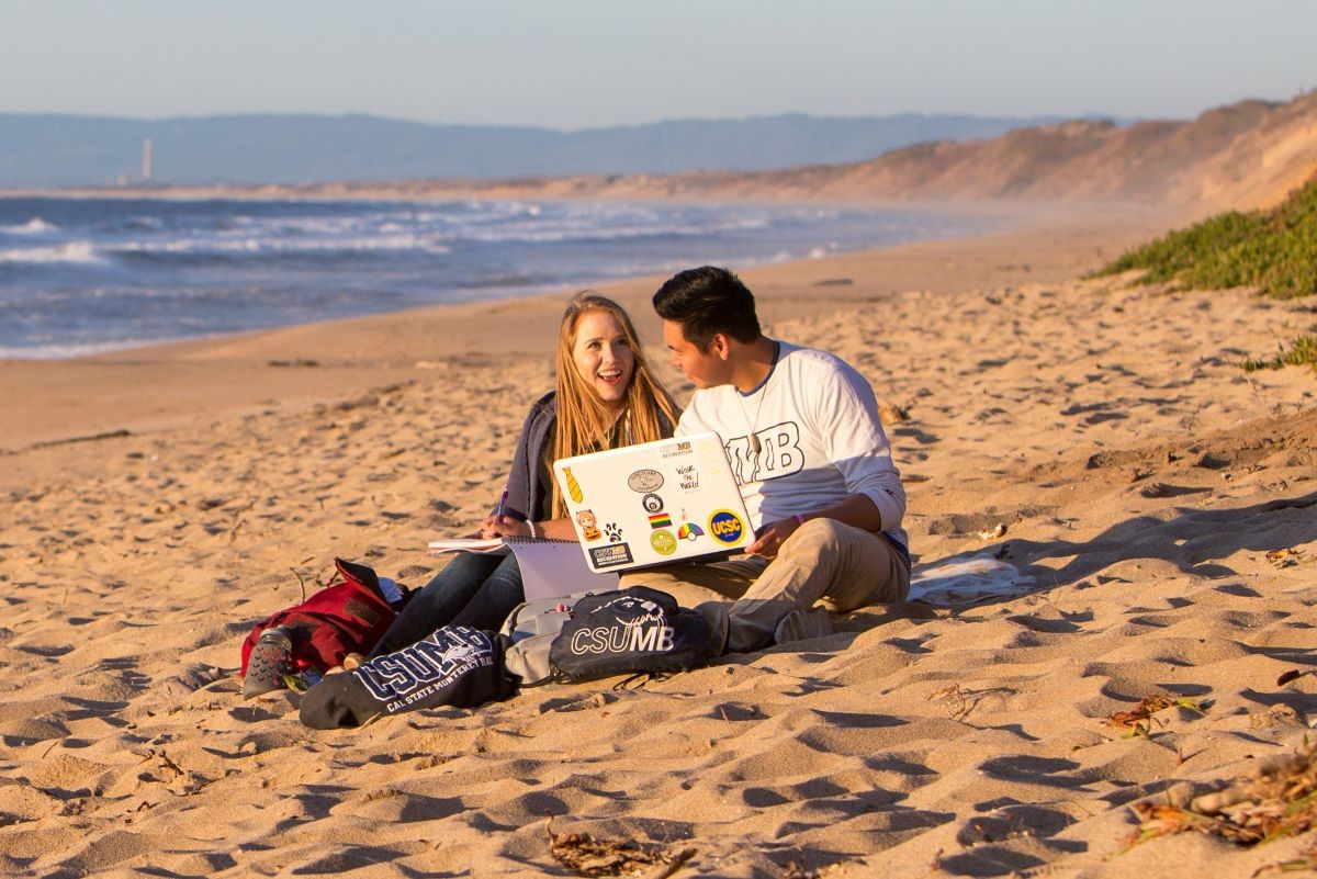Photo: Two students laughing and studying on the beach