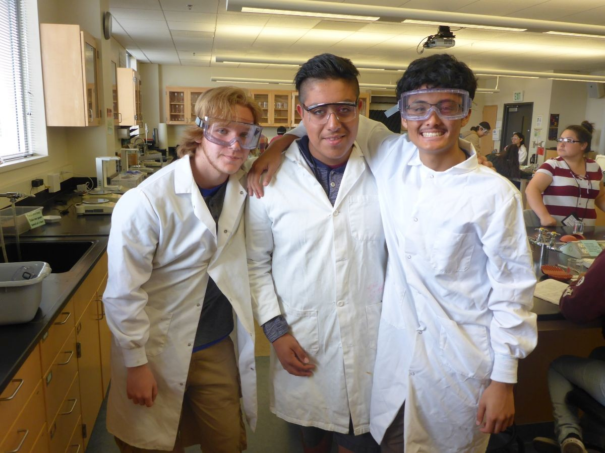 Students posing at a lab when they were conducting experiments.