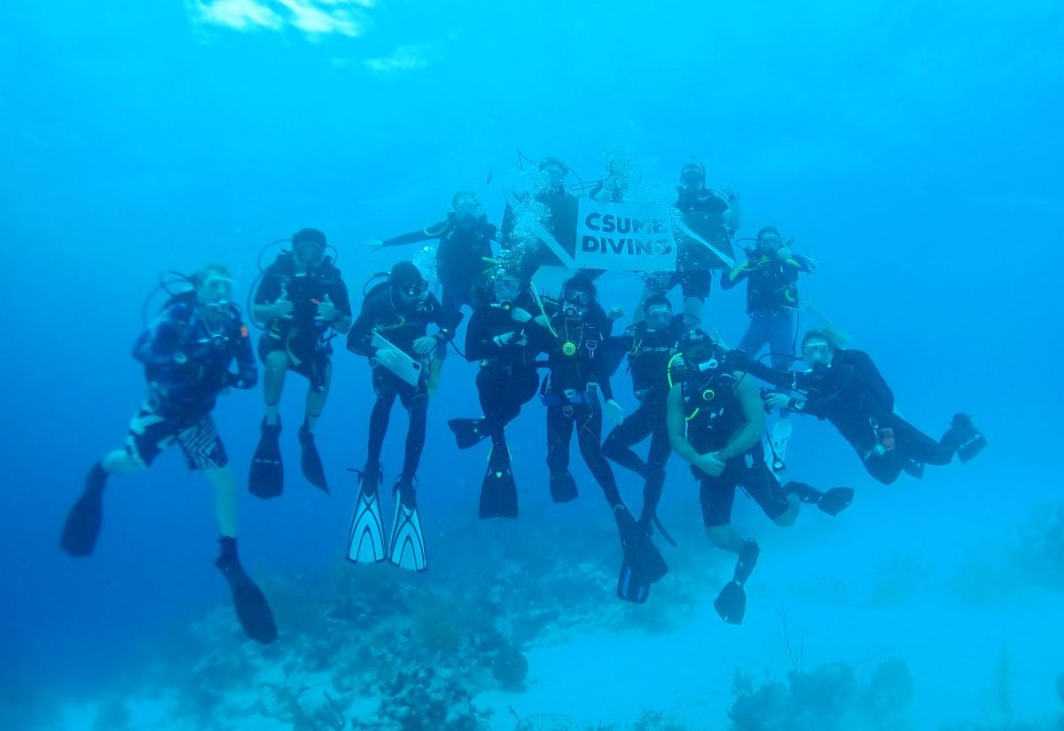 "A group of divers holding a sign that says ""CSUMB diving"""