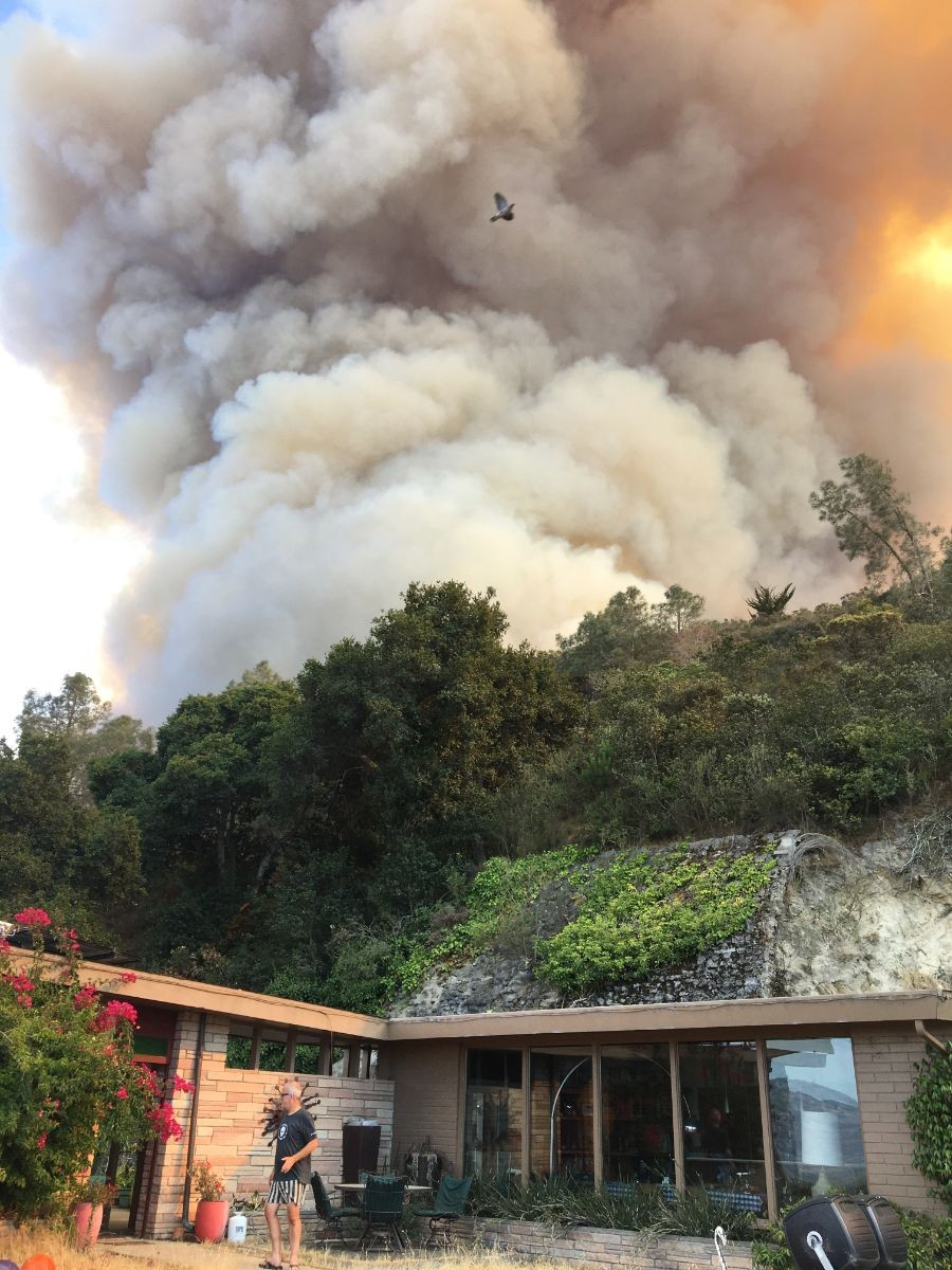Chip Lenno in front of their house as smoke rises behind the hillside