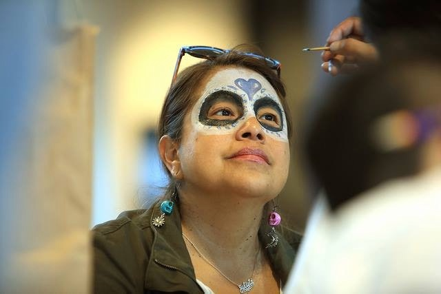 Someone painting a dia de los muertos face on a woman