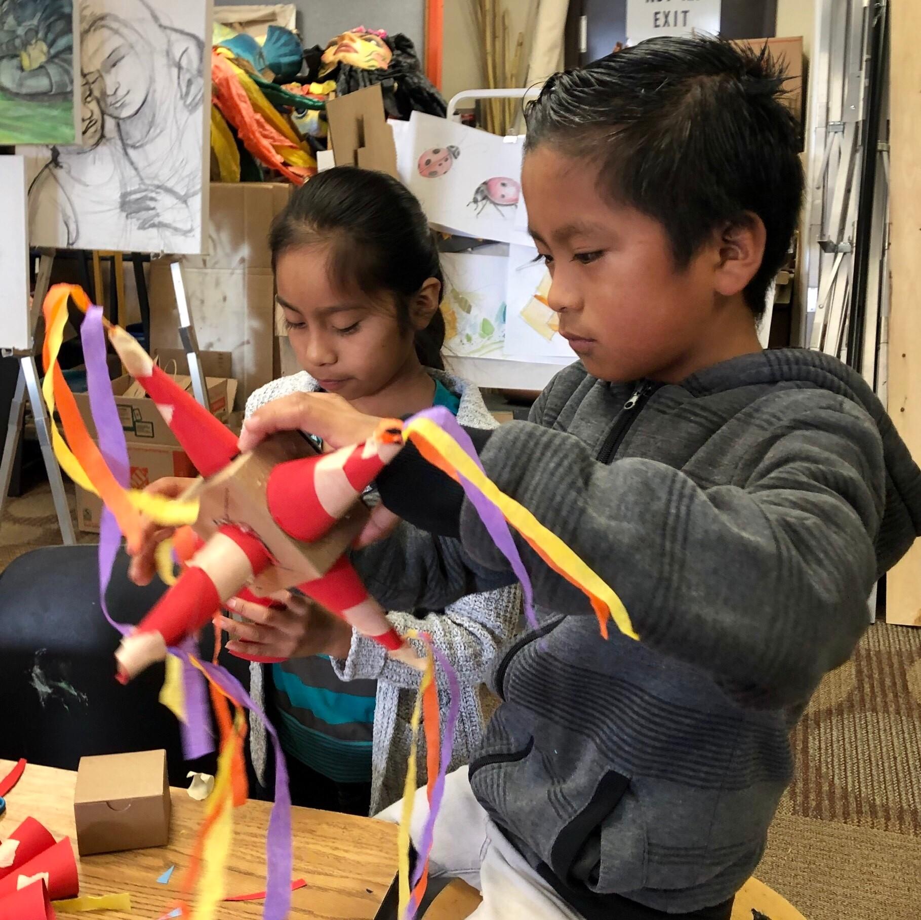 Two children focusing on making pinatas