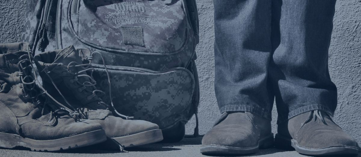 Photo: A man standing next to a National Guard backpack and boots