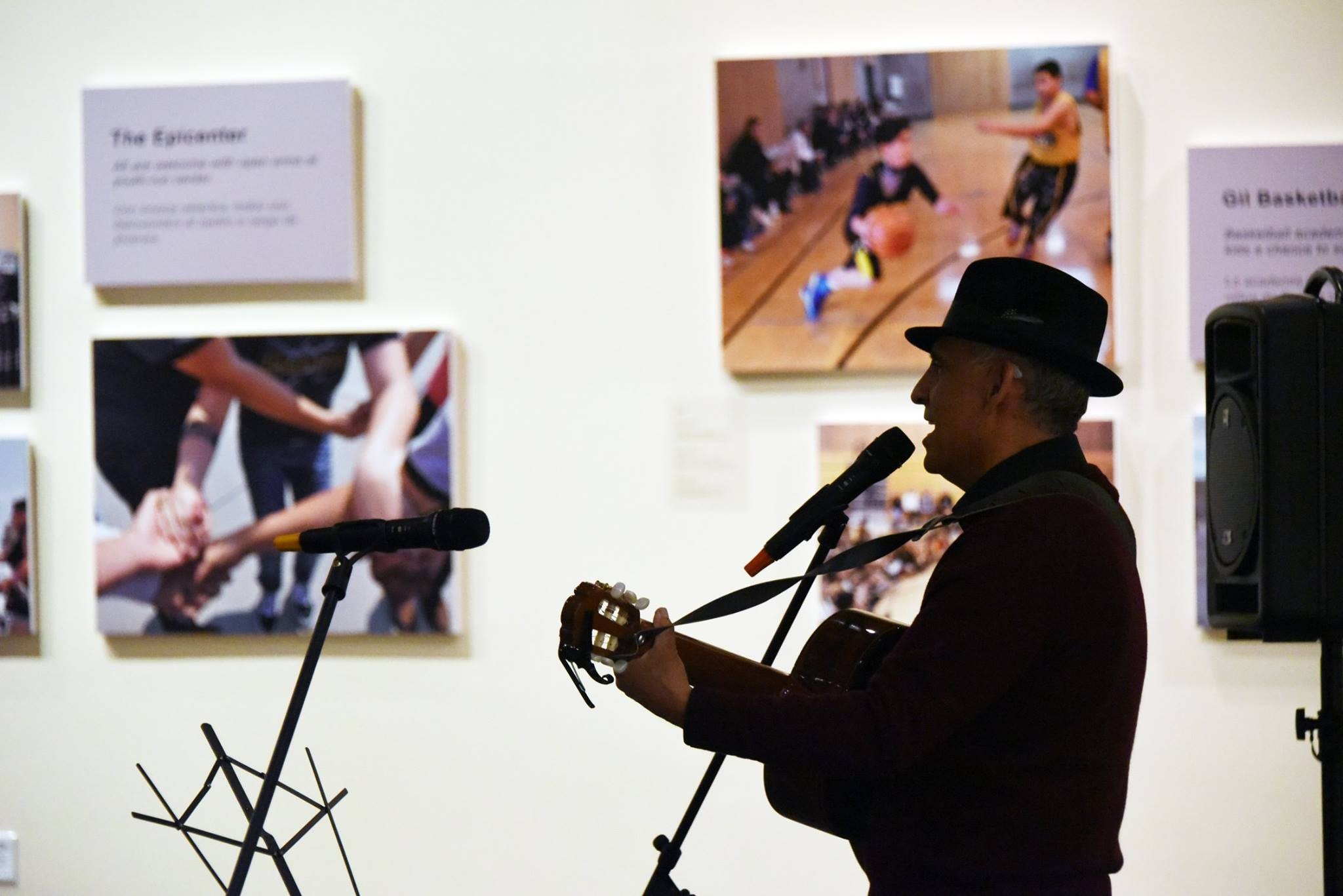 Man singing and playing guitar in a art gallery