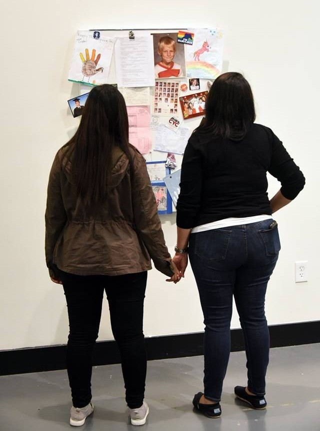 Two girls admiring the art while holding hands