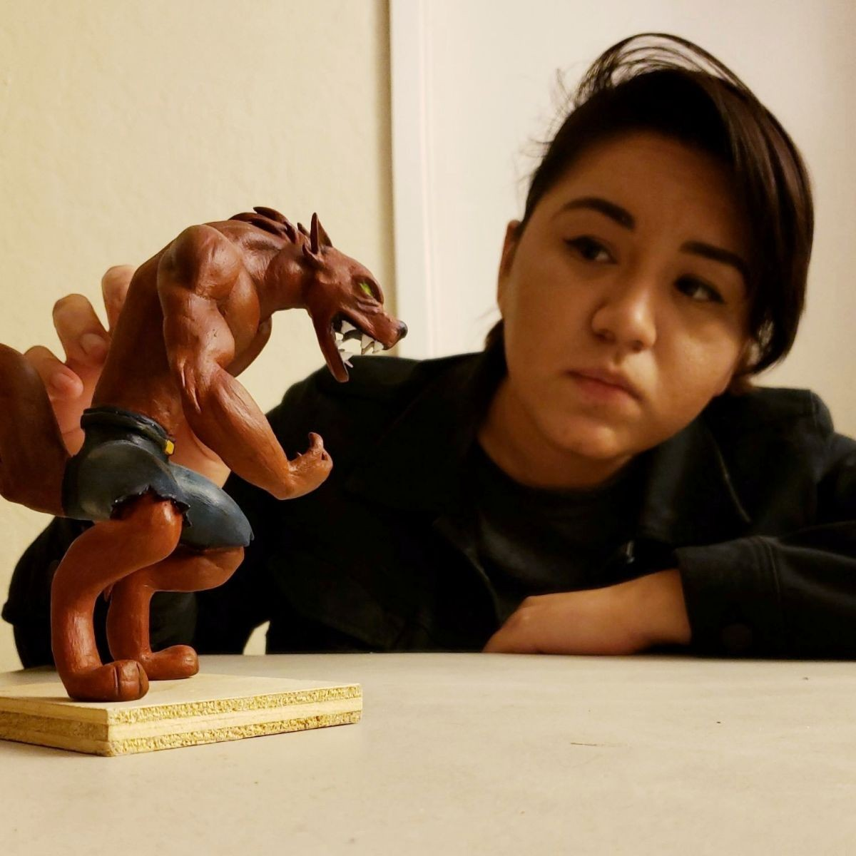Image of Joanna Gonzales show casing her art piece/figure