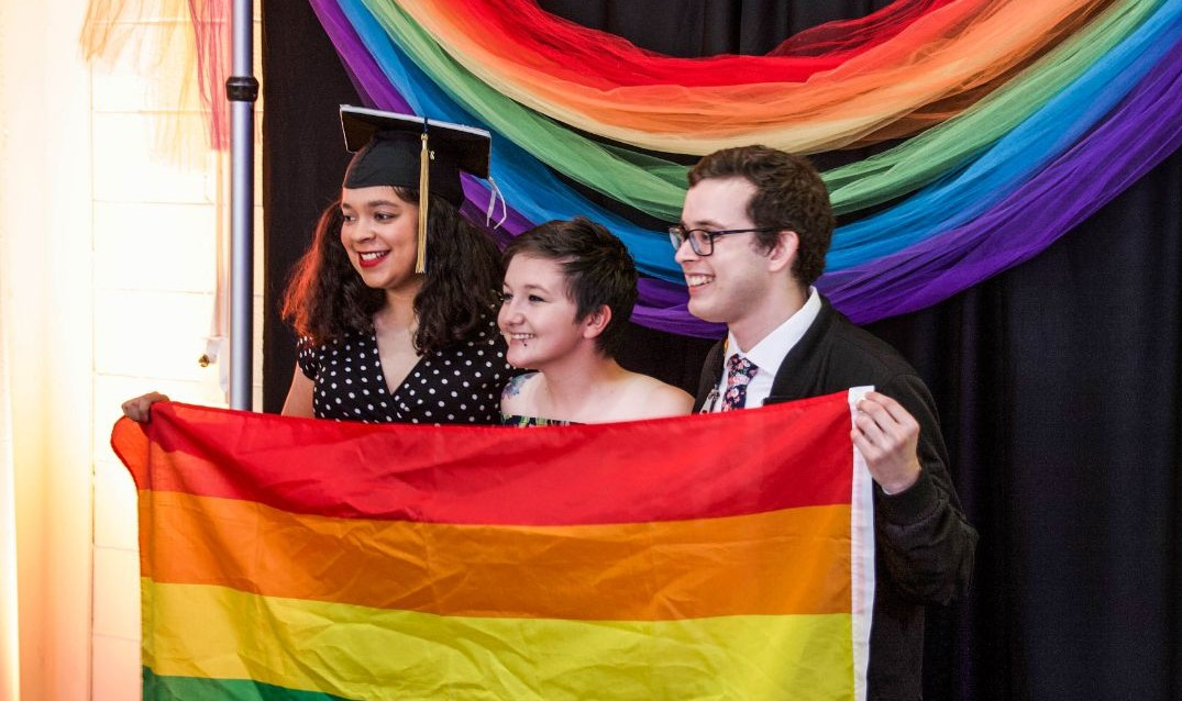 Students pose with rainbow flag at LGBTQ+ graduation celebration.