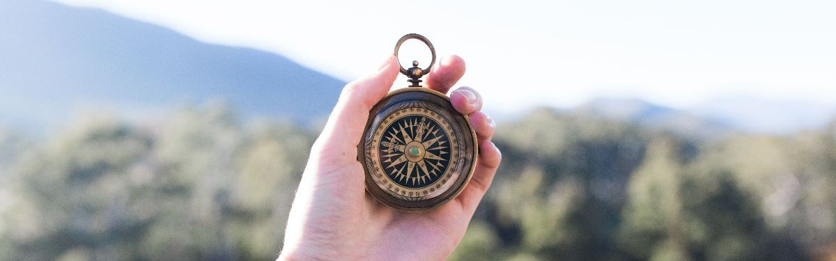 Photography of hand holding up a compass.
