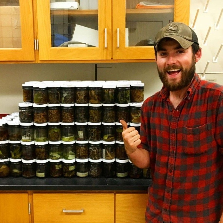 Student posing in front of lab soil samples