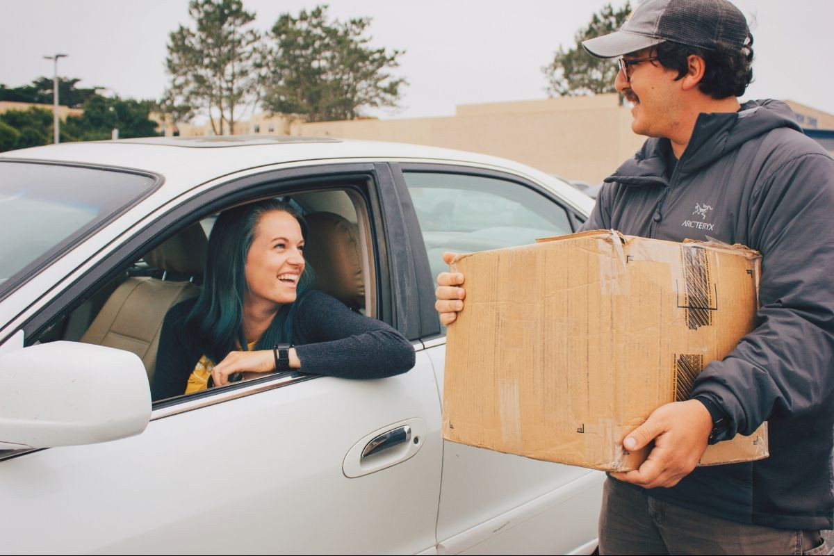 Two students moving in. One is in her car the other is holding a box