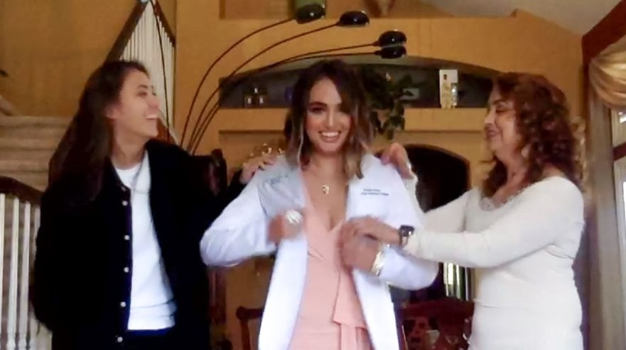 Student puts on her white coat