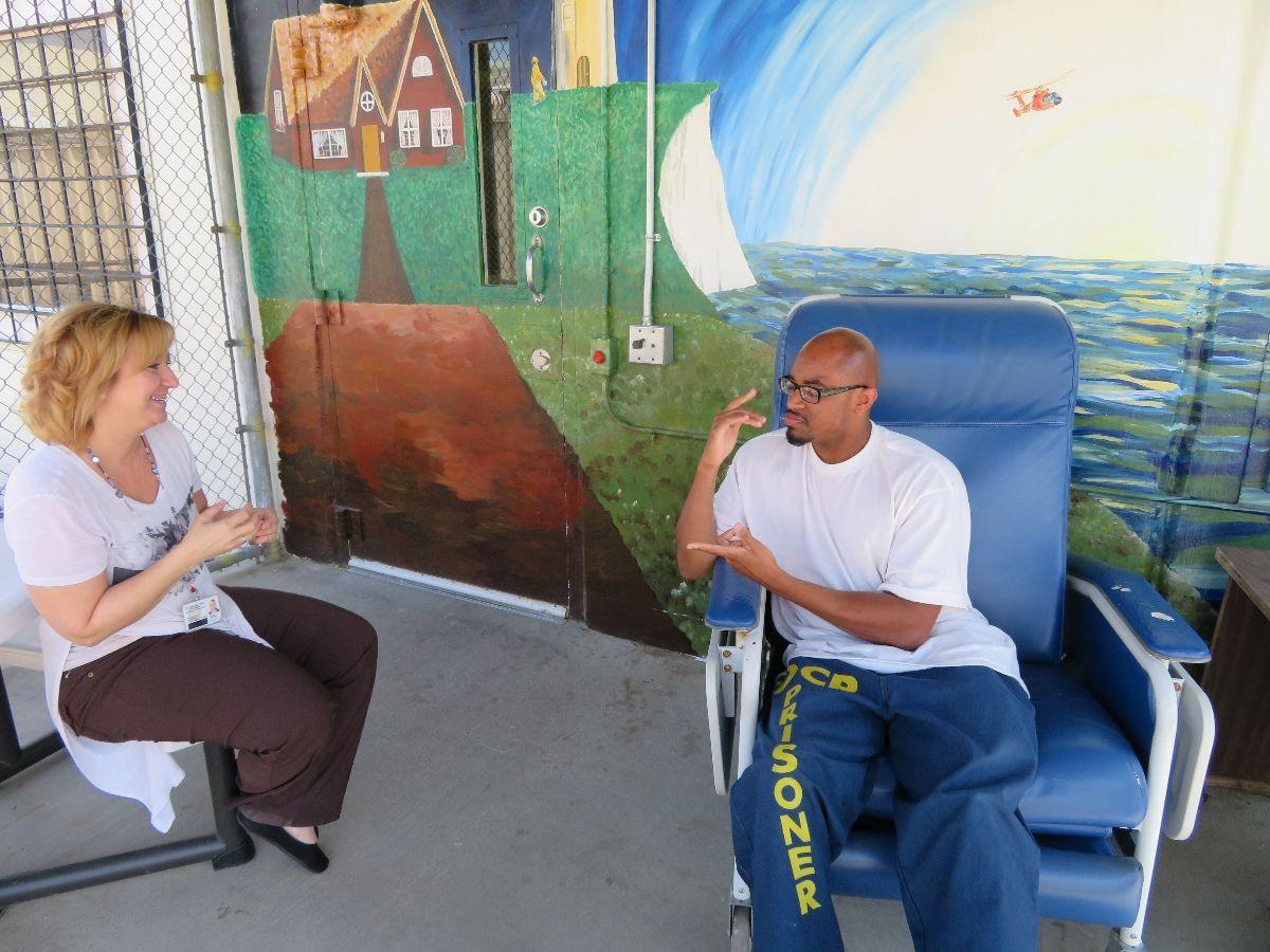 PCS worker Othello Watkins talks with his sign language interpreter.