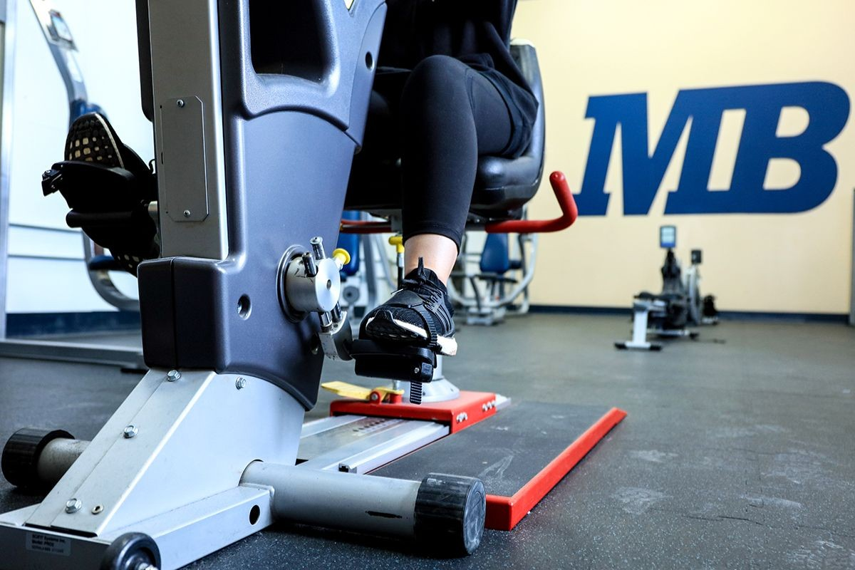"""Photo: A student using CSUMB gym equipment with """"MB"""" on a wall in the background"""