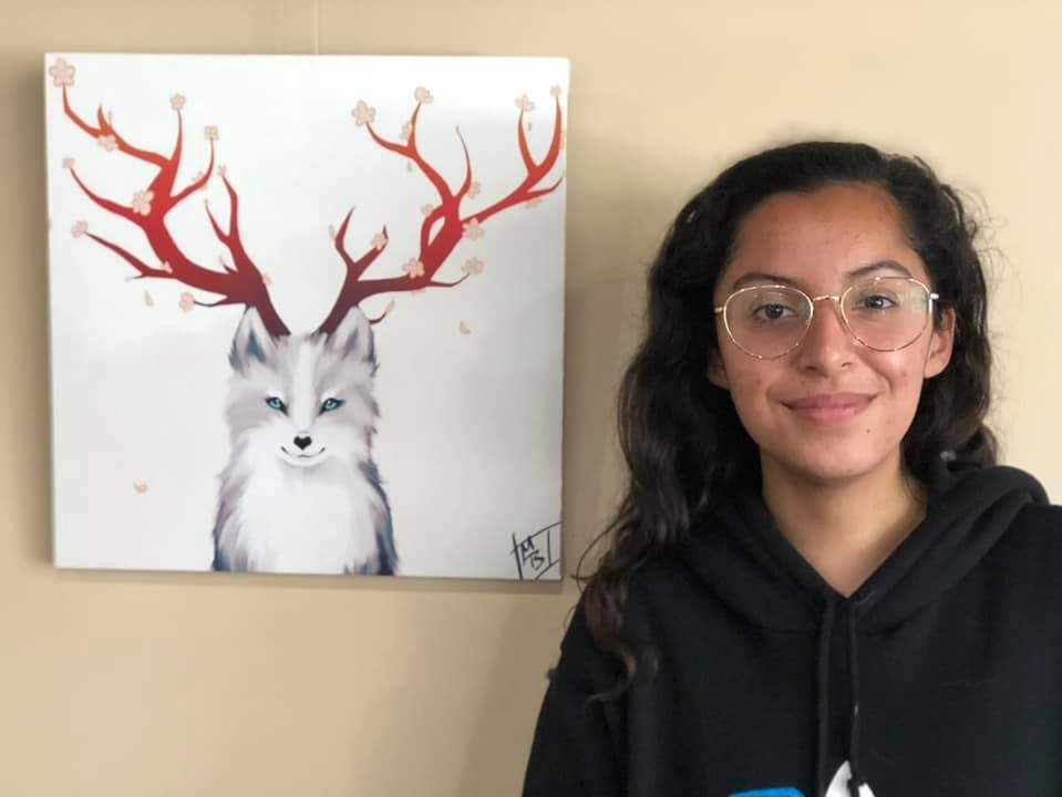 Photo of student standing next to her hung artwork