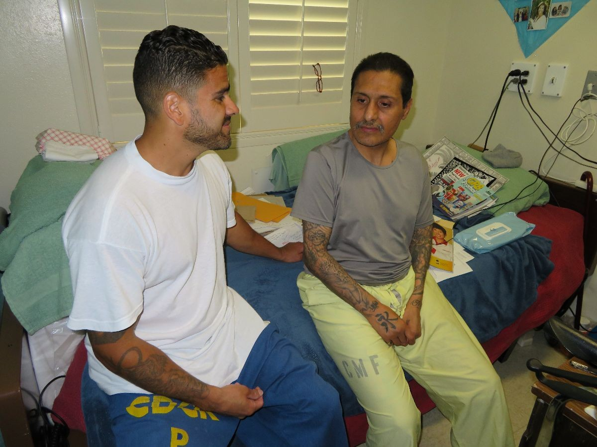 PCS worker Fernando Murillo talks with an inmate patient in the hospice unit.