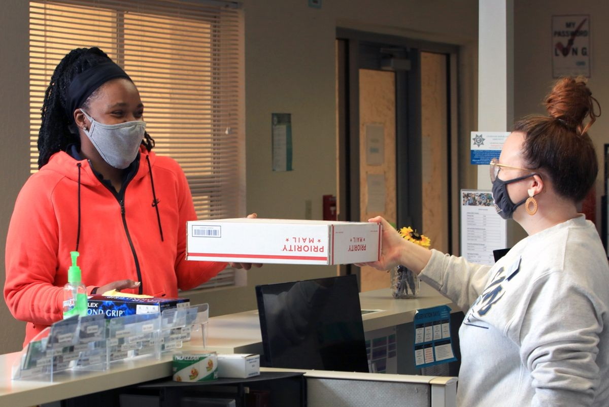 Photo: The coordinator of housing operations hands a package to an RA.