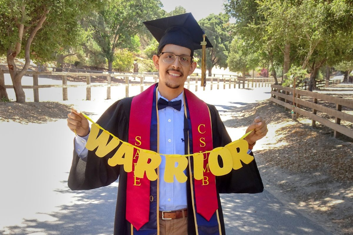 """Martin Cisneros in cap and gown, holding a banner that says """"Warrior."""""""