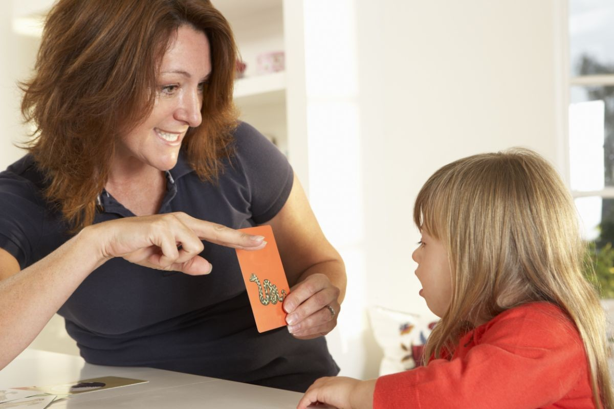 Speech therapist showing child a notecard with a snake on it.