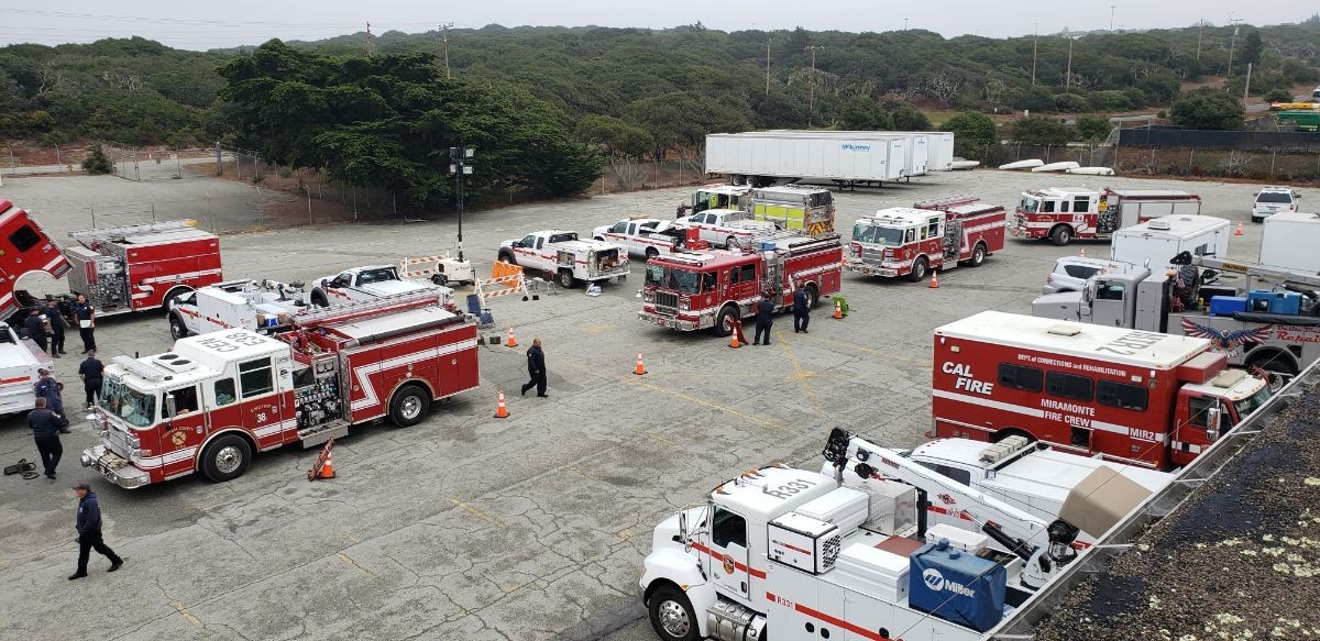 Firefighting and ground support vehicles in a motor pool at a CSUMB parking lot.